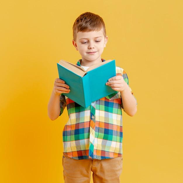 Vooraanzicht kleine jongen lezen Gratis Foto