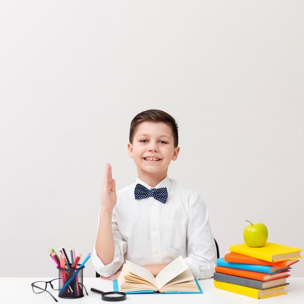 Vooraanzicht kleine jongen op bureau lezen Gratis Foto