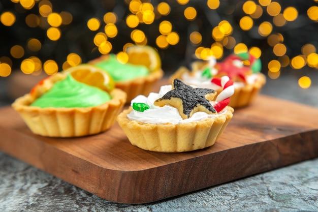 Vooraanzicht kleine kersttaartjes op snijplank op donkere geïsoleerde oppervlak kerstverlichting Gratis Foto