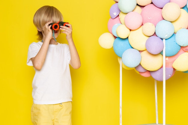 Vooraanzicht kleine schattige jongen in wit t-shirt samen met kleurrijke lucht ballonnen op gele bureau Gratis Foto