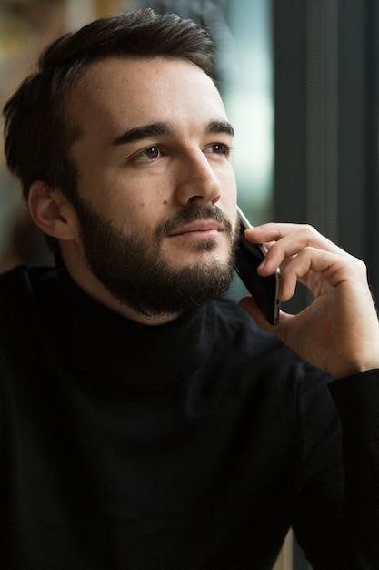 Vooraanzicht knappe man praten over de telefoon Gratis Foto
