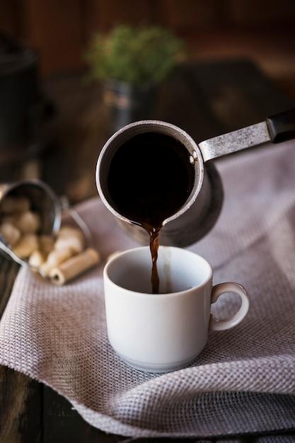 Vooraanzicht koffie uit een waterkoker gieten in een kopje Gratis Foto