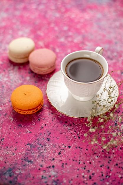 Vooraanzicht kopje thee in kopje op plaat met franse macarons op het roze bureau Gratis Foto