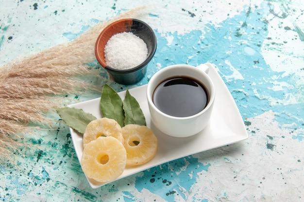 Vooraanzicht kopje thee met gedroogde ananasringen op lichtblauwe ondergrond Gratis Foto