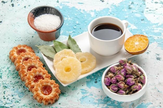 Vooraanzicht kopje thee met koekjes en gedroogde ananasringen op lichtblauwe ondergrond Gratis Foto
