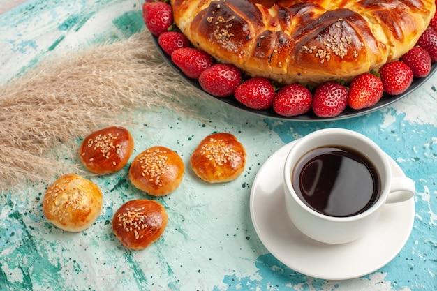 Vooraanzicht lekkere zoete taart met verse rode aardbeien en kleine cakes op het blauwe oppervlak Gratis Foto