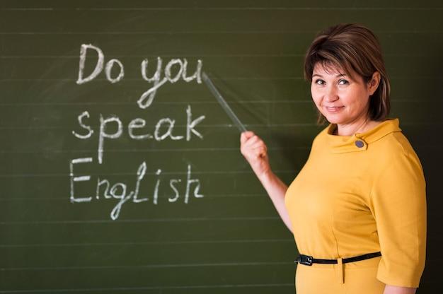 Vooraanzicht leraar schrijven op schoolbord Gratis Foto