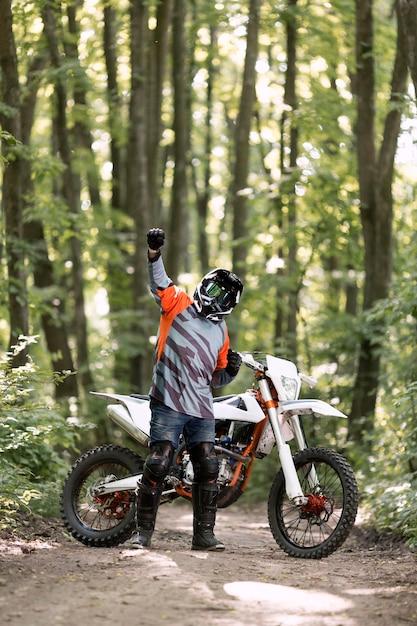 Vooraanzicht man blij om te fietsen in het bos Gratis Foto