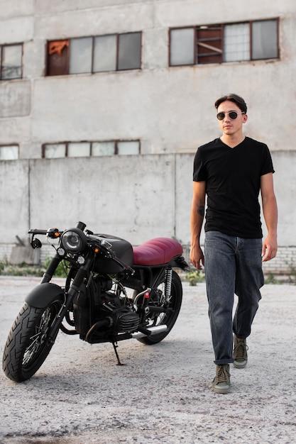 Vooraanzicht man die in de buurt van motorfiets Gratis Foto