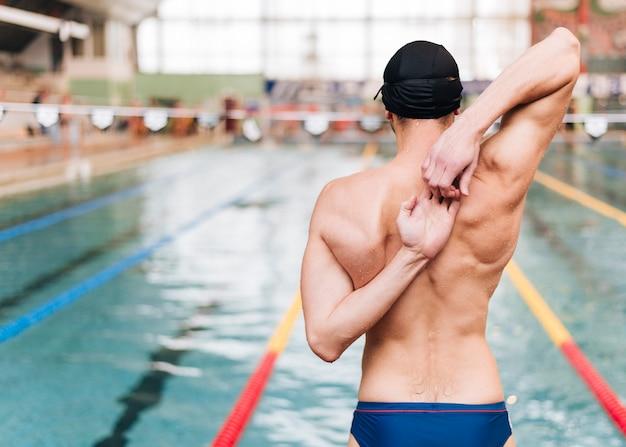 Vooraanzicht man die zich uitstrekt voor het zwemmen Gratis Foto
