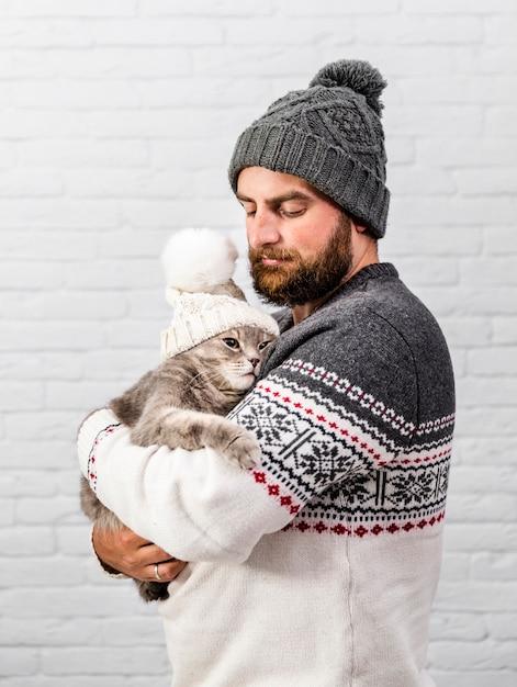 Vooraanzicht man en kitten bont muts dragen Gratis Foto