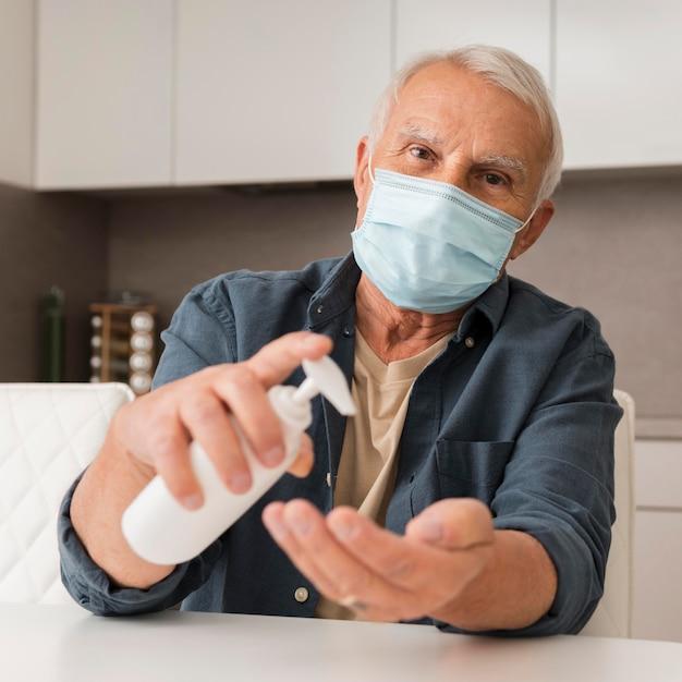 Vooraanzicht man met masker en ontsmettingsmiddel Gratis Foto