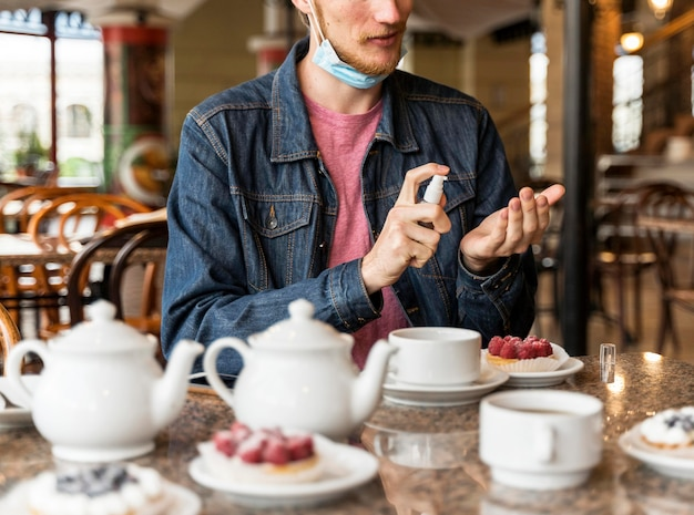 Vooraanzicht man zijn handen desinfecteren in het restaurant Gratis Foto