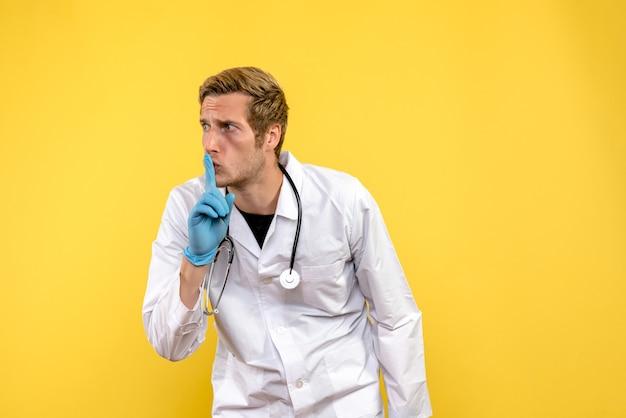 Vooraanzicht mannelijke arts die vraagt stil te zijn op gele achtergrondgezondheid menselijke virusdokter Gratis Foto
