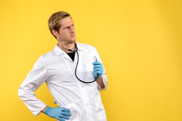 Vooraanzicht mannelijke arts verward op gele achtergrond gezondheid virus medic emotie Gratis Foto