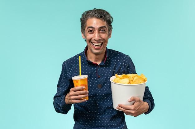 Vooraanzicht mannelijke bedrijf aardappel cips en soda op middelbare leeftijd lachen op een blauw oppervlak Gratis Foto