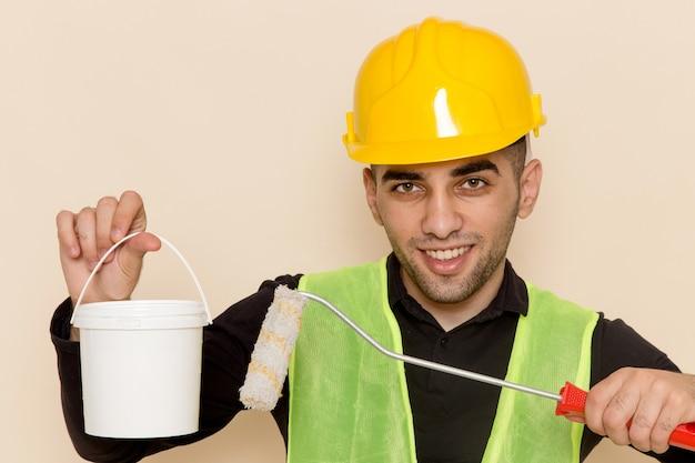 Vooraanzicht mannelijke bouwer in de gele borstel en verf van de helmholding op lichte achtergrond Gratis Foto
