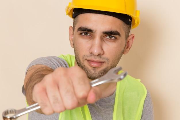 Vooraanzicht mannelijke bouwer in gele helm poseren met zilveren gereedschap op lichte achtergrond Gratis Foto