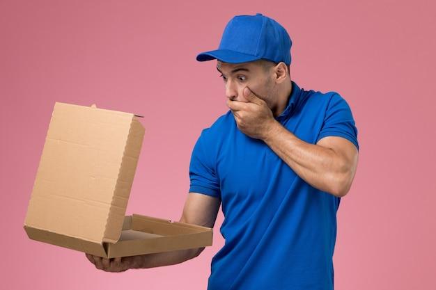 Vooraanzicht mannelijke koerier in blauw uniform bedrijf opening voedselleveringsdoos met geschokte uitdrukking op roze muur, uniforme levering van servicebanen Gratis Foto