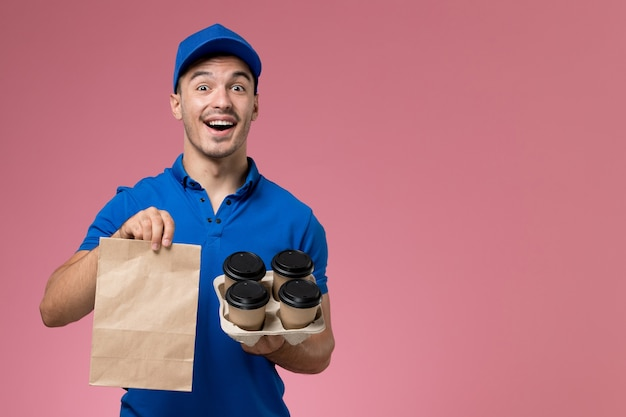 Vooraanzicht mannelijke koerier in blauw uniform met voedselpakket en koffie op de roze muur, uniforme dienstverlening Gratis Foto