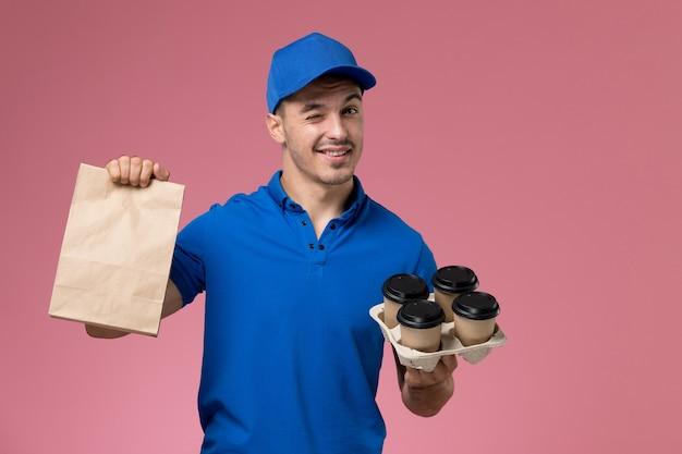 Vooraanzicht mannelijke koerier in blauw uniform met voedselpakket koffiekopjes op de roze muur, uniforme dienstverlener Gratis Foto