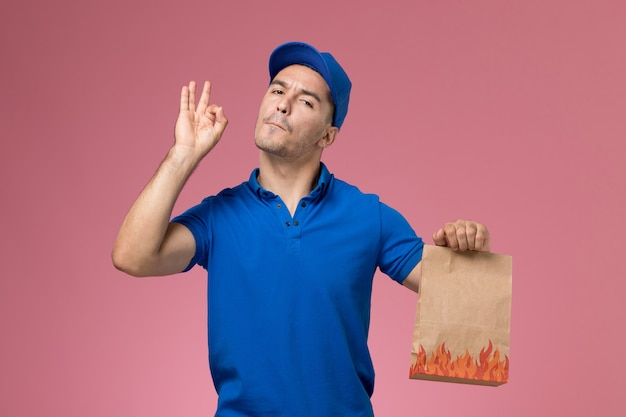 Vooraanzicht mannelijke koerier in blauw uniform voedselpakket houden op roze muur, werknemer uniforme dienstverlening Gratis Foto
