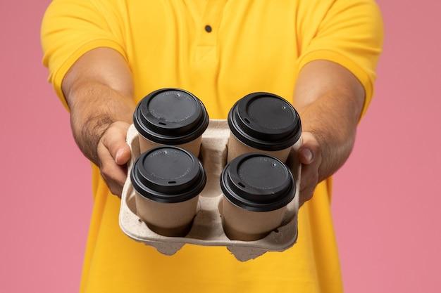 Vooraanzicht mannelijke koerier in geel uniform bezorgen koffiekopjes levering op het roze bureau Gratis Foto