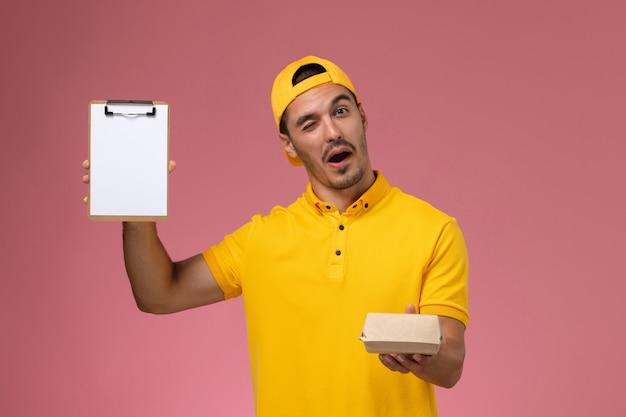 Vooraanzicht mannelijke koerier in geel uniform en cape die weinig notitieblok van het leveringsvoedselpakket op roze achtergrond houdt. Gratis Foto