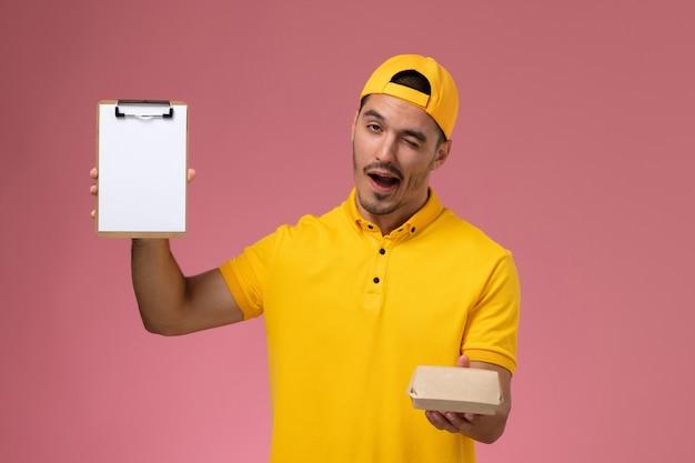 Vooraanzicht mannelijke koerier in geel uniform en cape die weinig pakket van het leveringsvoedsel en blocnote houden die op roze achtergrond knipogen. Gratis Foto