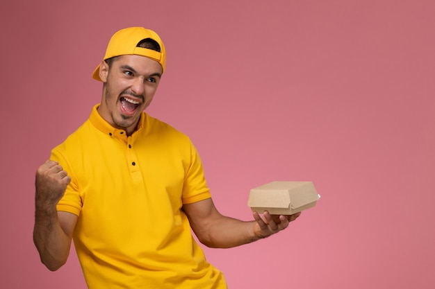 Vooraanzicht mannelijke koerier in geel uniform en cape die weinig voedselpakket houden dat op roze achtergrond toejuicht. Gratis Foto