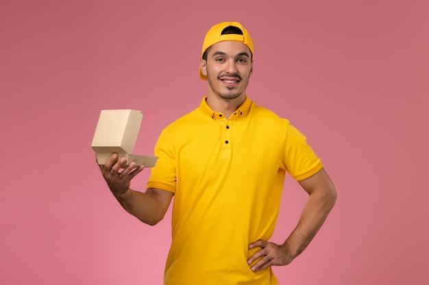 Vooraanzicht mannelijke koerier in geel uniform en cape die weinig voedselpakket houden en openen dat op de roze achtergrond glimlacht. Gratis Foto