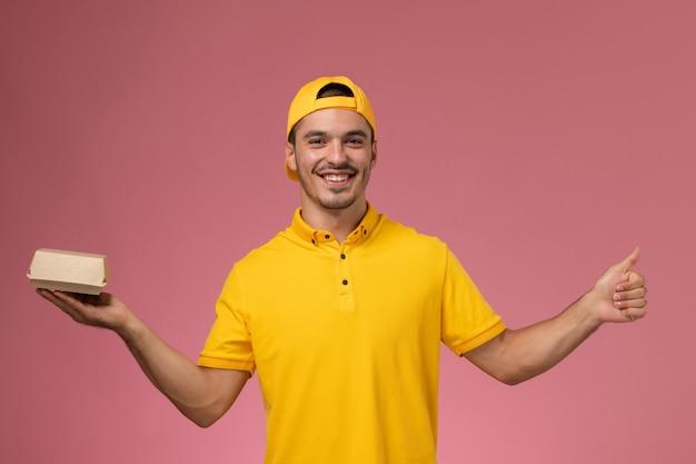 Vooraanzicht mannelijke koerier in geel uniform en cape die weinig voedselpakket houdt en op lichtroze achtergrond glimlacht. Gratis Foto
