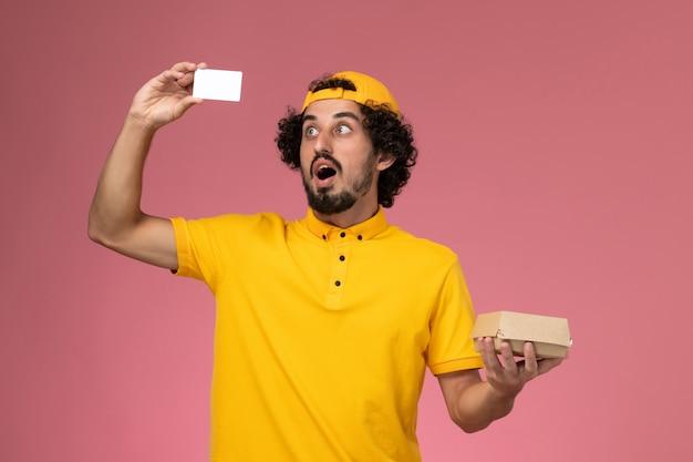 Vooraanzicht mannelijke koerier in geel uniform en cape met kaart en weinig bezorgvoedselpakket op zijn handen op de lichtroze achtergrond. Gratis Foto