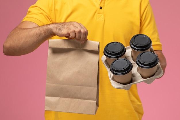 Vooraanzicht mannelijke koerier in geel uniform houden voedselpakket en levering koffiekopjes op roze achtergrond Gratis Foto