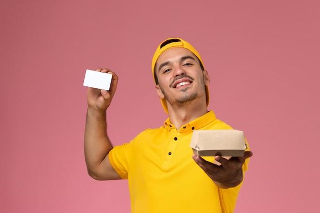 Vooraanzicht mannelijke koerier in gele uniforme holdingskaart en klein voedselpakket op roze achtergrond. Gratis Foto