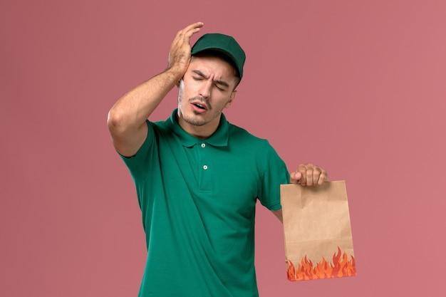 Vooraanzicht mannelijke koerier in groen uniform bedrijf papier voedselpakket met hoofdpijn op lichtroze achtergrond Gratis Foto