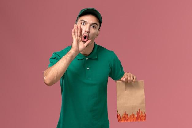 Vooraanzicht mannelijke koerier in groen uniform bedrijf papier voedselpakket op de lichtroze achtergrond Gratis Foto