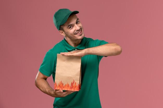 Vooraanzicht mannelijke koerier in groen uniform bedrijf papier voedselpakket op de roze achtergrond Gratis Foto