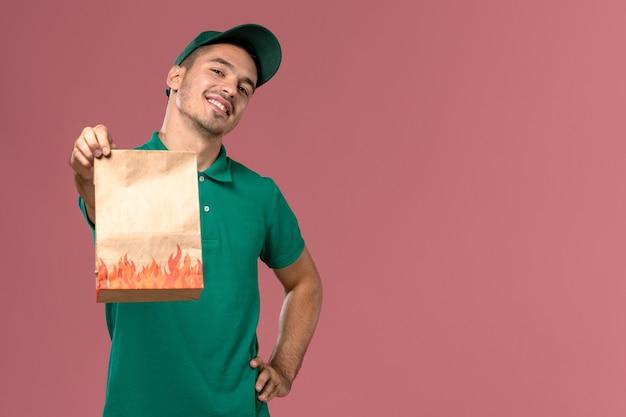 Vooraanzicht mannelijke koerier in groen uniform papier voedselpakket houden en gewoon poseren op roze achtergrond Gratis Foto