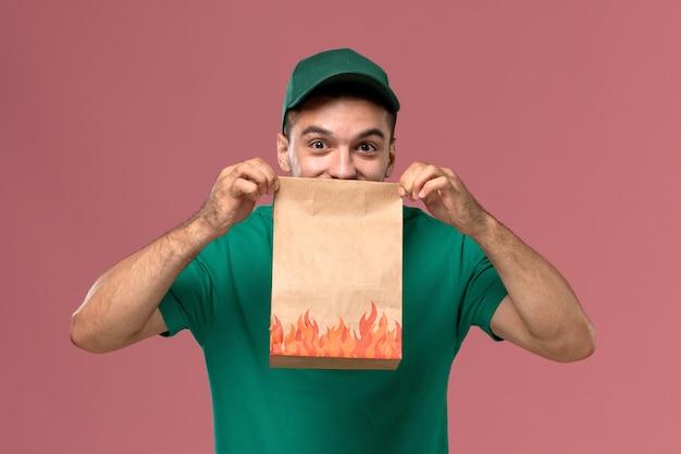 Vooraanzicht mannelijke koerier in groen uniform papier voedselpakket houden en glimlachend op roze achtergrond Gratis Foto