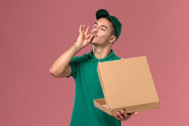Vooraanzicht mannelijke koerier in groen uniform voedseldoos vasthouden en openen op het lichtroze bureau Gratis Foto