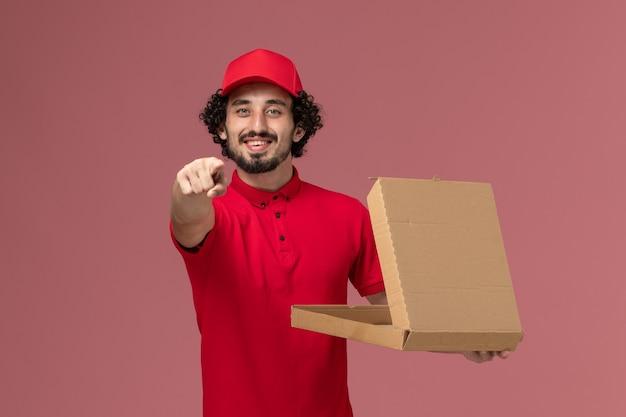 Vooraanzicht mannelijke koerier in rood overhemd en cape die lege doos van het leveringsvoedsel houden en op de roze muur glimlachen Gratis Foto
