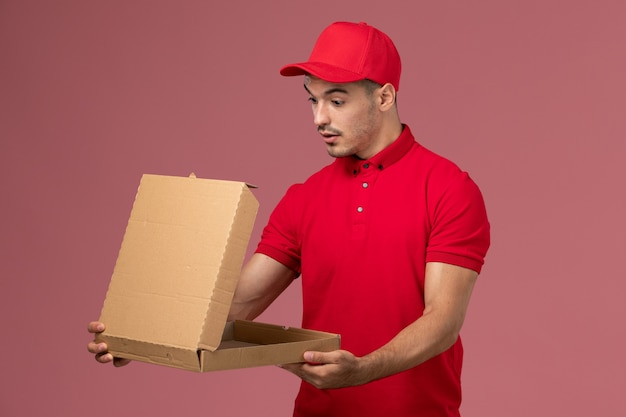 Vooraanzicht mannelijke koerier in rood uniform en cape met voedselleveringsdoos op roze muur levering mannelijke uniform werknemer Gratis Foto