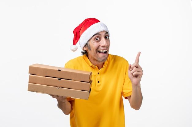 Vooraanzicht mannelijke koerier met pizzadozen op wit bureau baan uniforme dienstverlening Gratis Foto