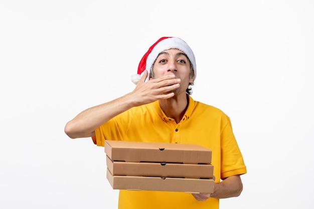 Vooraanzicht mannelijke koerier met pizzadozen op witte eenvormige de dienstlevering van de muurbaan Gratis Foto