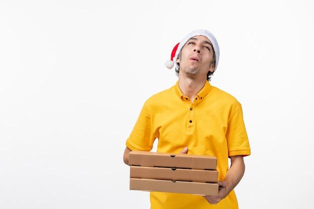 Vooraanzicht mannelijke koerier met pizzadozen op witte muur uniforme baanbezorgservice Gratis Foto