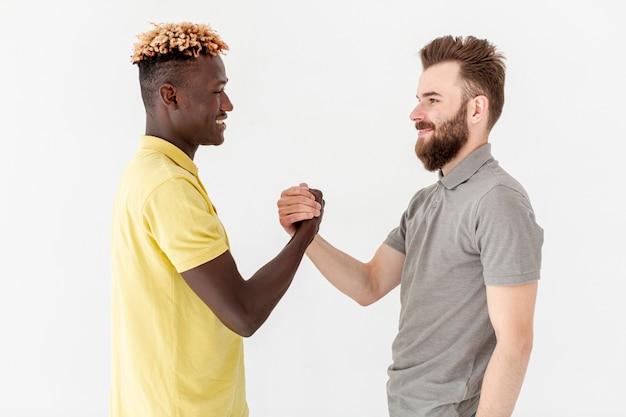 Vooraanzicht mannelijke vrienden handen schudden Gratis Foto