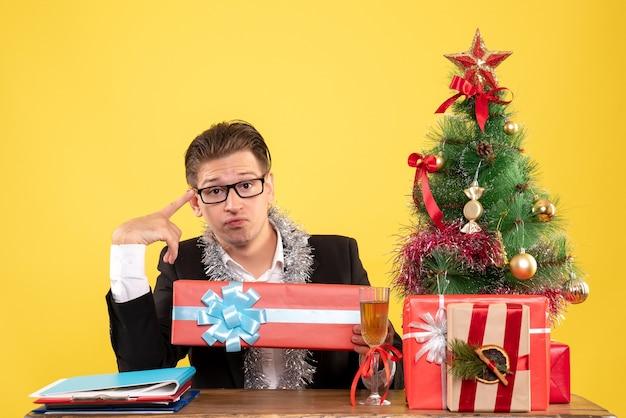 Vooraanzicht mannelijke werknemer zitten en houden kerstcadeau Gratis Foto