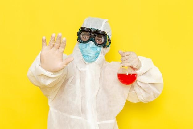 Vooraanzicht mannelijke wetenschappelijke werker in speciaal beschermend pak met kolf met rode oplossing op geel bureau Gratis Foto