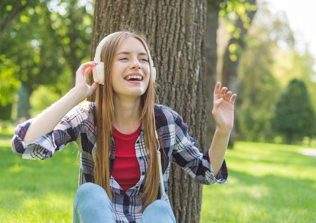 Vooraanzicht meisje buiten luisteren naar muziek Gratis Foto